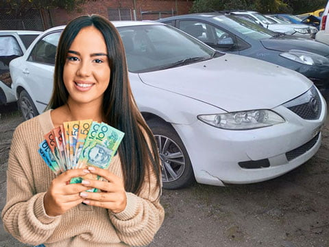 Woman holding up loads of cash she received for scrapping her car with us