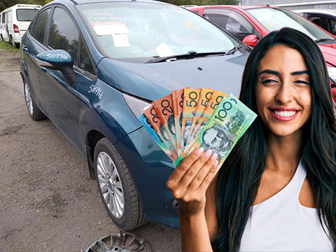 Woman holding up money she made after selling your Ford to our car buyers.